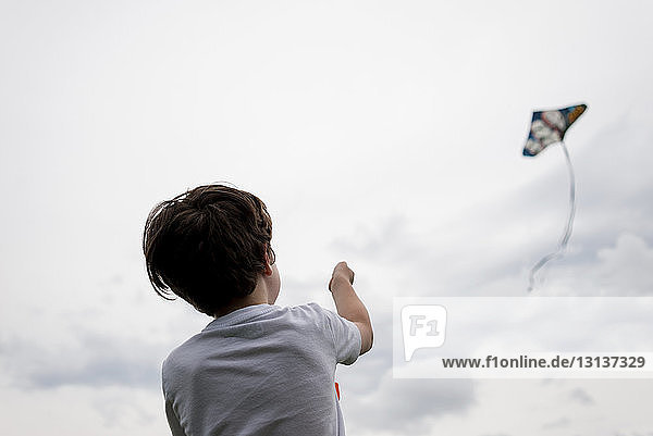 Rear view of boy flying kite in cloudy sky