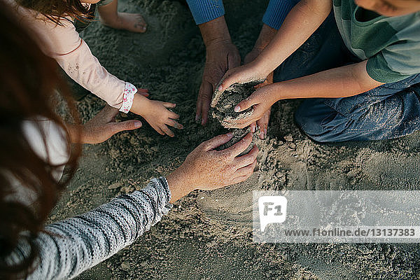 Cropped image of family playing in sand at beach