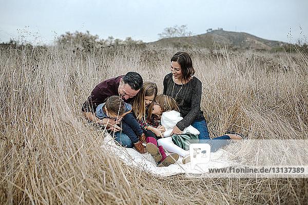 Happy family sitting on grassy field against sky