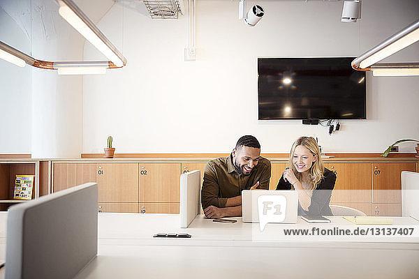 Kollegen benutzen Laptop-Computer,  während sie im Büro am Tisch sitzen