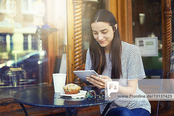 Smiling woman using digital tablet while sitting by table at sidewalk cafe