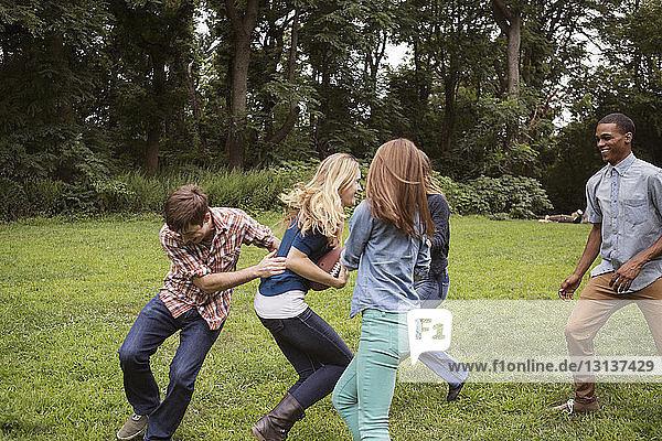 Fröhliche Freunde spielen Fussball auf Rasen
