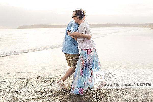 Seitenansicht eines glücklichen Paares  das sich umarmt  während es am Strand am Ufer steht