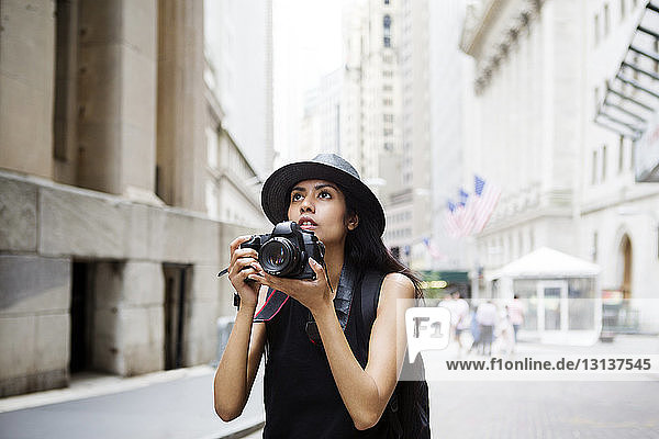 Woman with camera standing on city street