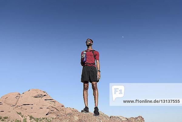 Niedrigwinkelansicht eines männlichen Wanderers  der eine Wasserflasche hält  während er auf einer Felsformation vor klarem blauen Himmel steht