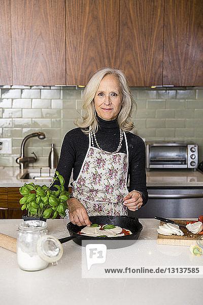 Porträt einer selbstbewussten älteren Frau  die zu Hause in der Küche Pizza zubereitet