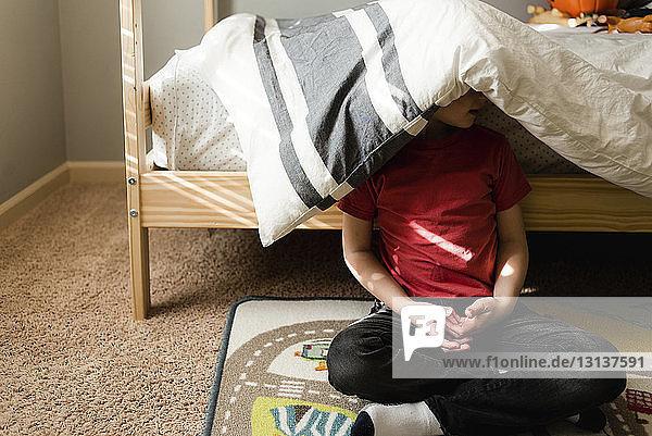 Junge  der mit einer Decke auf dem Kopf gegen das Etagenbett sitzt