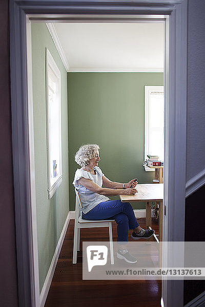 Senior woman using smart phone while sitting on chair at home seen through doorway