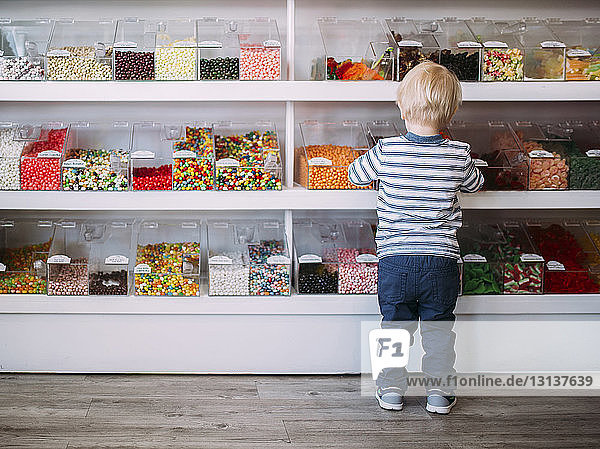 Rear view of boy standing against shelves in store
