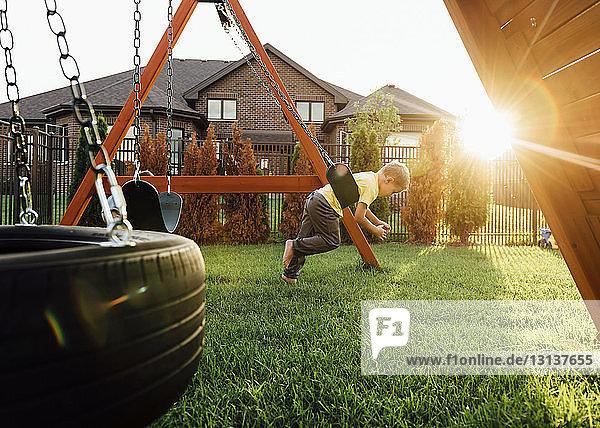 Boy playing on swing at yard
