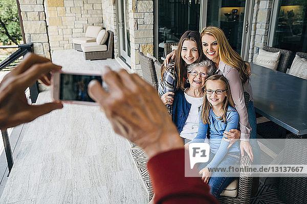 Abgetrennte Hände eines älteren Mannes fotografieren glückliche Familie durch ein Smartphone auf der Veranda