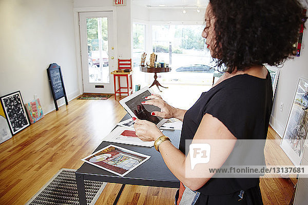 Side view of female owner using tablet computer while standing in gallery