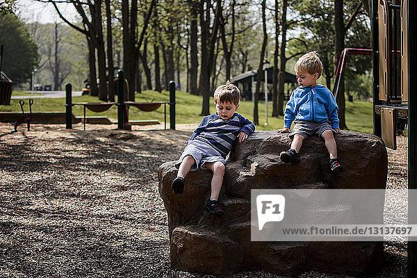 Brüder sitzen auf einem Felsen auf einem Spielplatz