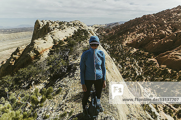 Female hiker with backpack wearing jacket and cap while standing on mountain during sunny day