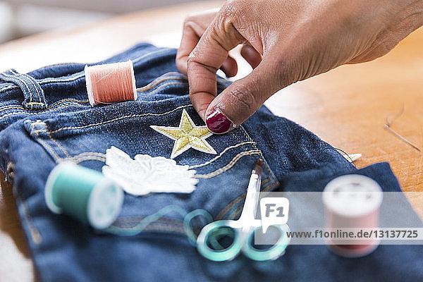 Geschorene Hand einer Frau  die bei Tisch sternförmige Textilpatches auf Jeans legt