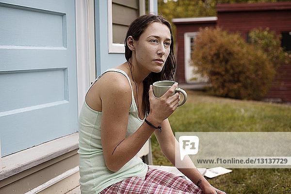 Nachdenkliche Frau hält Kaffeetasse  während sie vor dem Haus sitzt