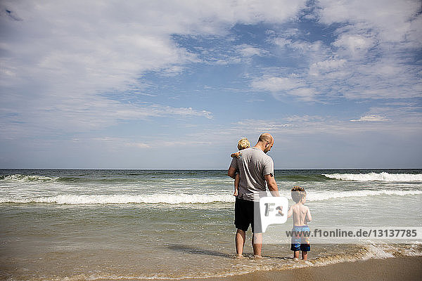 Rear view of family enjoying at beach against sky on sunny day