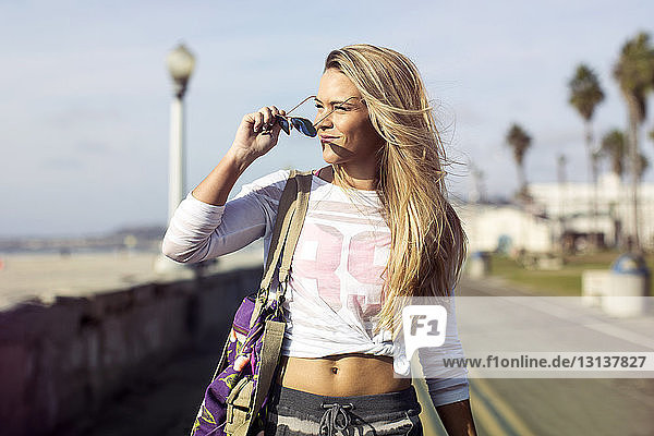 Thoughtful young woman holding sunglasses while walking on street