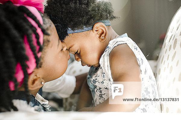 Nahaufnahme eines Mädchens  das seine Schwester küsst  die zu Hause auf einem Stuhl sitzt