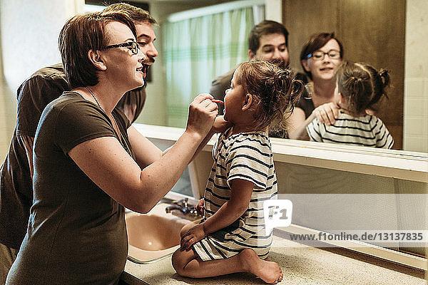 Vater steht bei der Mutter und putzt der Tochter im Badezimmer die Zähne