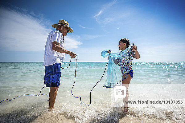 Grandfather holding rope of fishing net carried by granddaughter while standing on shore at beach against sky