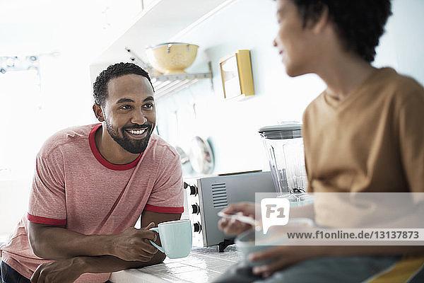 Glücklicher Vater schaut den Sohn an  während er Kaffee an der Küchentheke trinkt