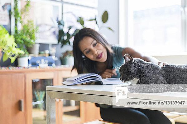 Frau streichelt Katze im Heimbüro
