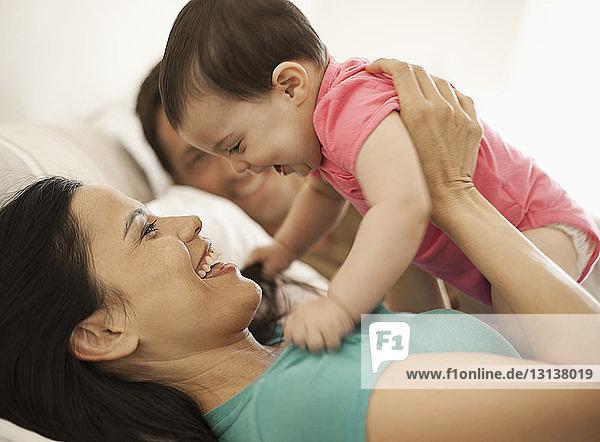 Mutter spielt mit Tochter  während sie zu Hause im Bett liegt