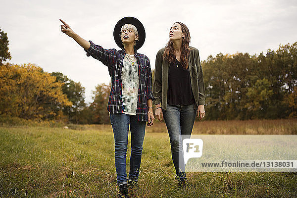 Young woman pointing and showing friend while walking on field