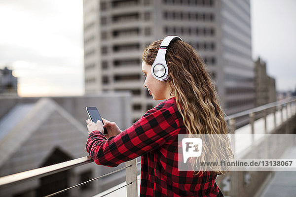 Seitenansicht einer Frau  die ein Smartphone benutzt  während sie am Geländer auf der Terrasse steht