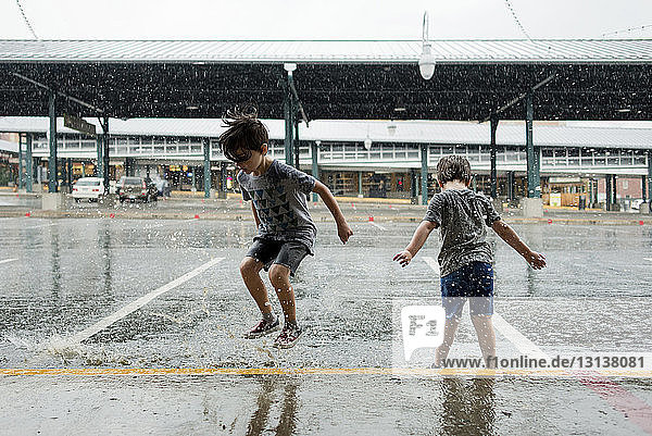 Happy brothers playing in parking lot during monsoon