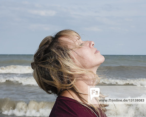Side view of woman with eyes closed standing by sea against sky during sunny day