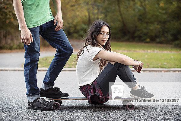 Frau sitzt auf Skateboard mit Mann auf der Strasse