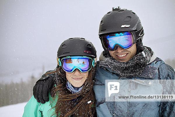 Porträt von Freunden auf verschneitem Berg gegen Himmel