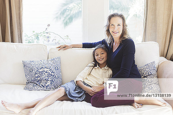 Portrait of smiling mother and daughter sitting on sofa at home