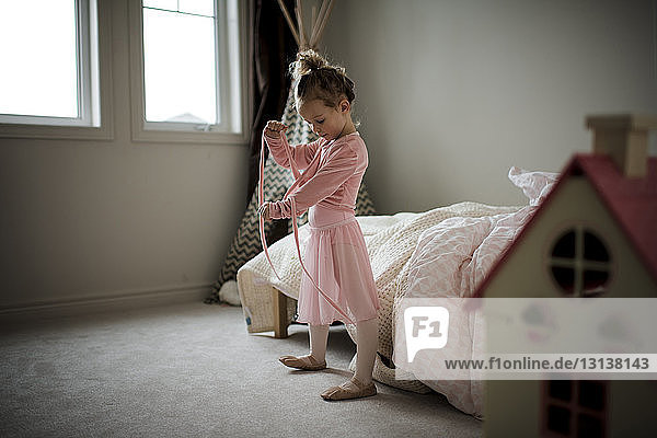 Girl in ballet costume standing at home