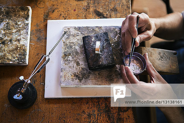 Ausgeschnittenes Bild eines Handwerkers  der in der Werkstatt auf einer Bank an Schmuck arbeitet Ausgeschnittenes Bild eines Handwerkers, der in der Werkstatt auf einer Bank an Schmuck arbeitet
