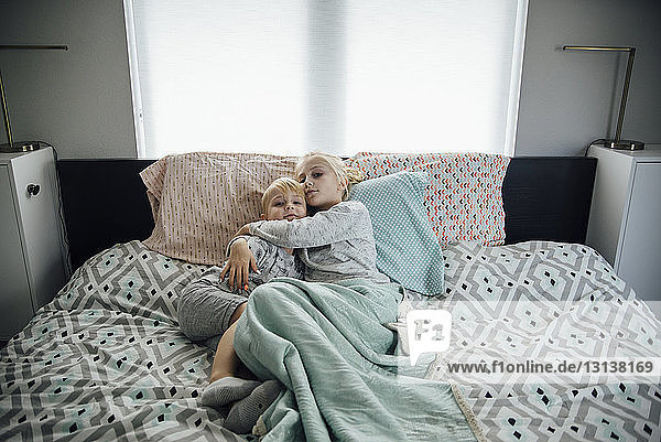 High angle portrait of sister embracing brother while lying on bed at home