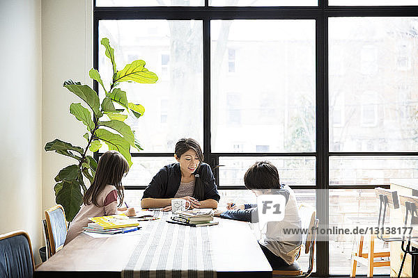 Mother teaching children on table at home on sunny day