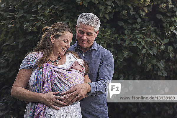 Couple with newborn daughter standing against plants at backyard