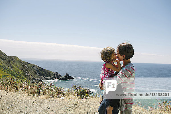 Side view of mother carrying daughter while standing on cliff by sea against sky