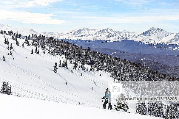 Frau fährt Ski gegen schneebedeckte Berge