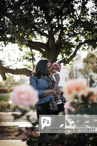 Mutter trägt Tochter  während sie im Park an Bäumen steht