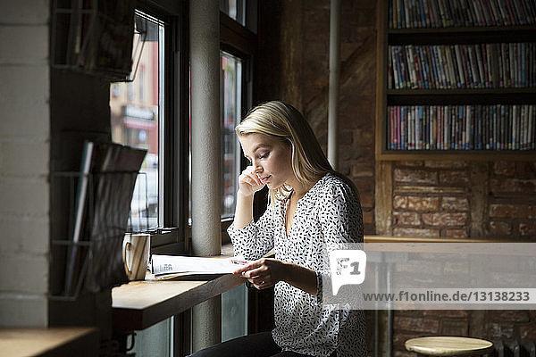 Seriöse Frau liest Zeitung bei Tasse am Tisch im Cafe