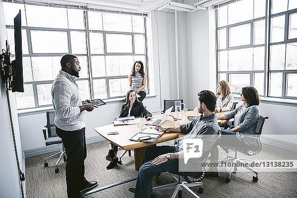 Kollegen diskutieren mit einem Geschäftsmann  der im Sitzungssaal eine Präsentation hält