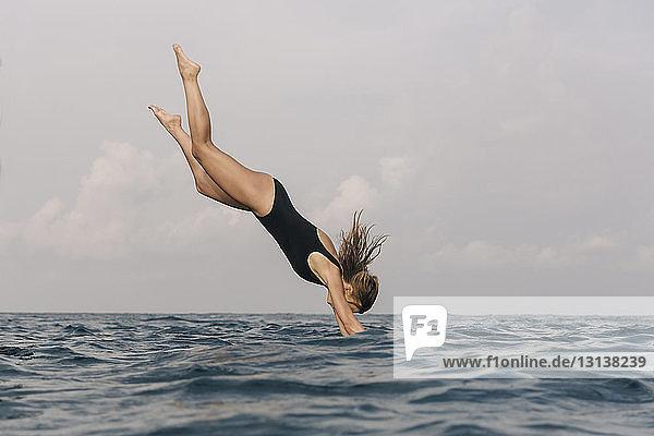 Seitenansicht einer Frau  die gegen den Himmel ins Meer taucht