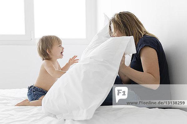 Glückliche Mutter und Tochter spielen mit Kissen  während sie zu Hause im Bett sitzen