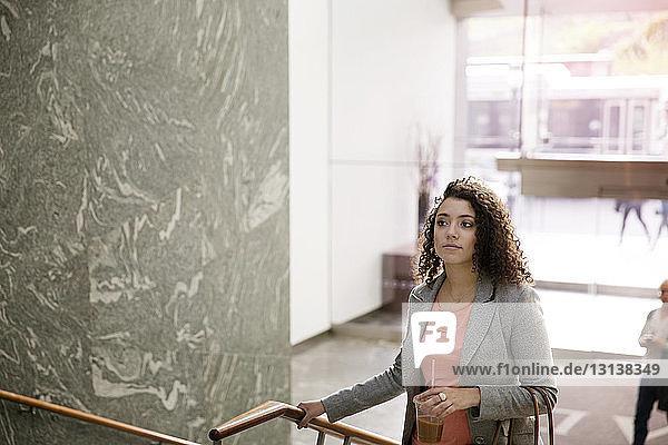 Nachdenkliche Geschäftsfrau steigt in modernem Gebäude auf
