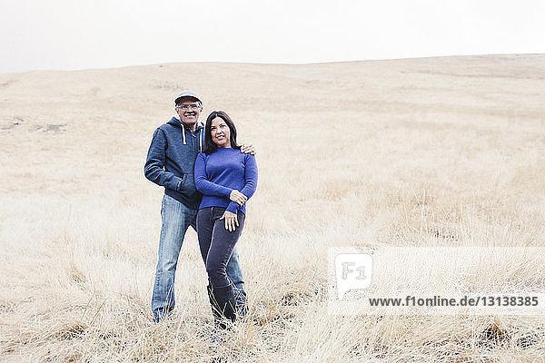 Porträt eines selbstbewussten Paares auf dem Feld stehend