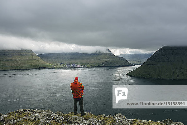 Hiker looking at view while standing on cliff against cloudy sky
